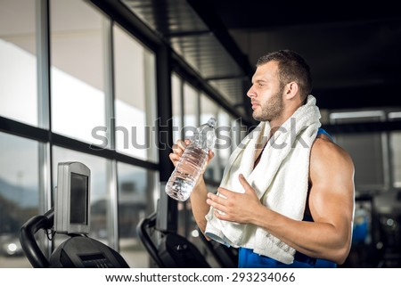 Young adult man drinking bottle of water on threadmill in gym. - stock photo