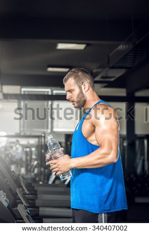Young adult man drinking bottle of water on treadmill in gym. - stock photo