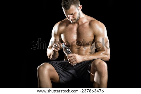 Young adult man drinking water and sitting on gym ball. - stock photo