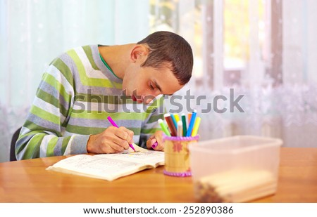 young adult man engages in self study, in rehabilitation center - stock photo