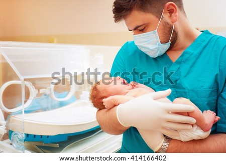 young adult man holding a newborn baby in hospital - stock photo