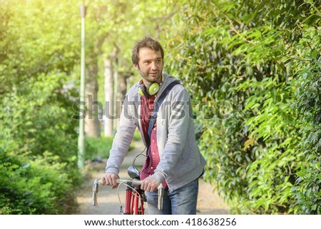 young adult man riding a bike in the city street - stock photo