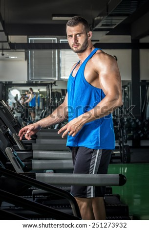 Young adult man running on treadmill in gym