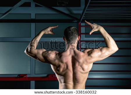 Young adult man showing back of body while posing in gym - stock photo