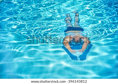 Young adult man swimming underwater in the pool alone/Man in swimming pool - stock photo