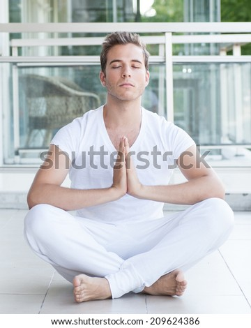 Young adult meditating with hands together. Facing palms.