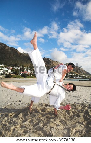Young adult men with black belt practicing fighting on the beach on a sunny day - Movement on extremeties of fighters - stock photo