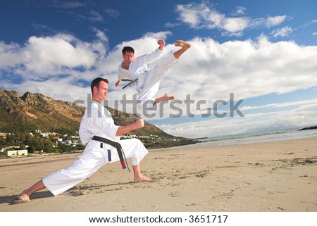 Young adult men with black belt practicing on the beach on a sunny day. The man doing the flying kick in the background has movement. Focus on the standing man - stock photo