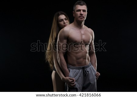 Young adult muscular man and woman. Sexy couple on black background - stock photo