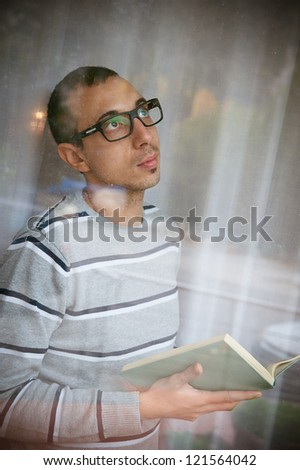 Young adult pensive man reads a book at window, Italy - stock photo