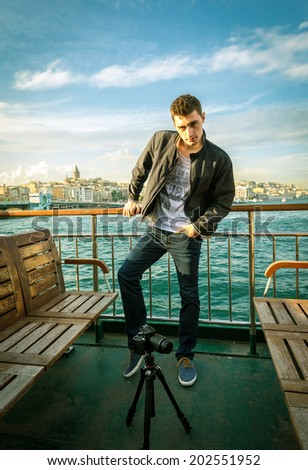 Young adult photographer standing at ship fence in Istanbul. - stock photo