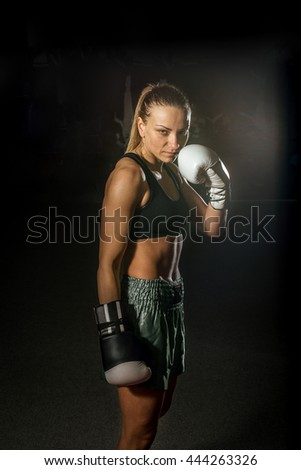 Young adult sexy female takes portrait photo during kickboxing exercise - stock photo