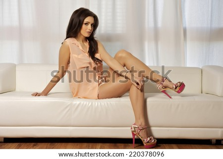 Young adult slim sexy and attractive sensuality brunette woman in pink blouse on the white sofa in luxury style apartment - stock photo