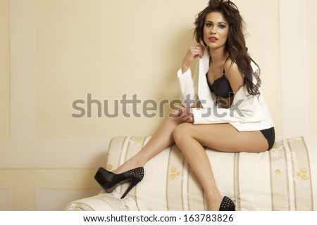 Young adult slim sexy and attractive sensuality brunette woman in  white jacket and black lingerie posing on sofa in luxury apartment