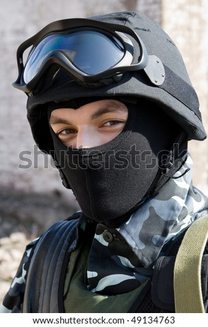 Young adult soldier in full ammunition - mask, helmet,glasses,vest - stock photo