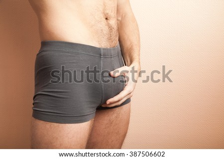 Young adult sporty man  in gray boxer underpants holding his genitals with hand, close-up studio photo with selective focus