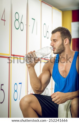 Young adult tired man drinking water in locker room of gym.