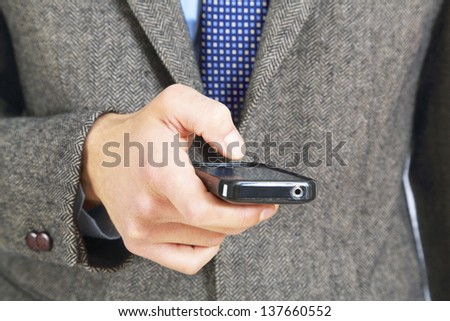 young adult type with the thumb on his smart phone - stock photo