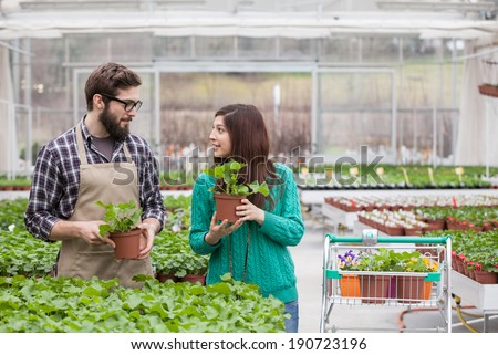 Young adult woman being assisted by manual worker at garden center - stock photo