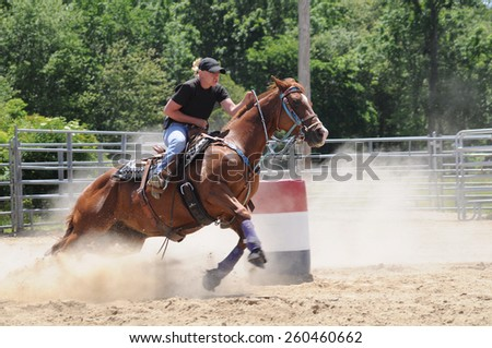 Young adult woman galloping past a barrel during a barrel race - stock photo
