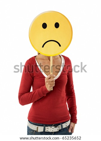 young adult woman holding sad emoticon on white background. Vertical shape, waist up - stock photo