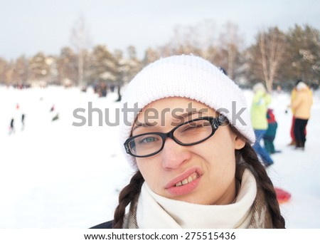 young adult woman in a white winter cap and glasses - stock photo