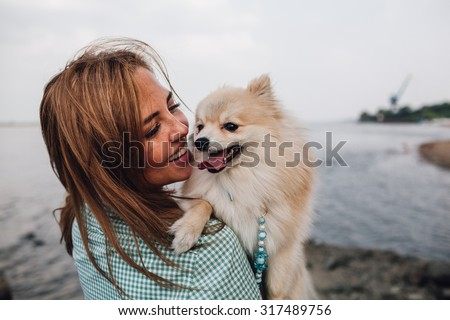 Young adult  woman is holding a dog on her shoulder. Woman turned back around. - stock photo