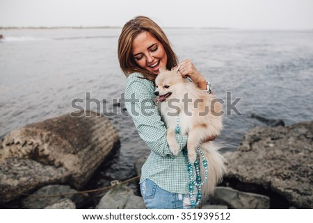 Young adult  woman is holding a little dog on her hands - stock photo