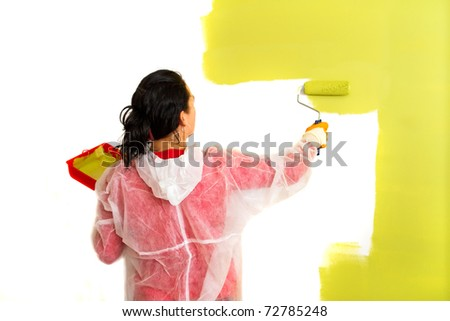 Young adult woman painting interior wall of house - stock photo