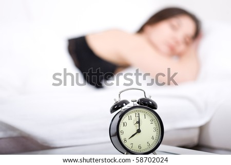 young adult woman sleeping in bed - stock photo