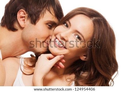 Young adult woman smiling and holding hand near mouse with boyfriend kissing her - stock photo