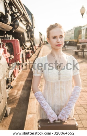 Young adult woman standing near old retro vintage train Caucasian girl down the stairs Cute slim female waiting wagon with small luggage Elegant Lady wear long white dress - stock photo