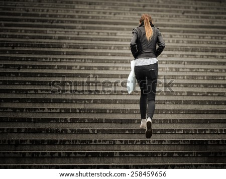 Young adult woman walks up the stairs (in the rain) - stock photo