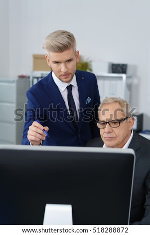 Young adult worker showing man in eyeglasses something on large wide computer monitor screen