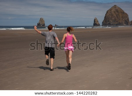 Young adults playing on the beach - stock photo