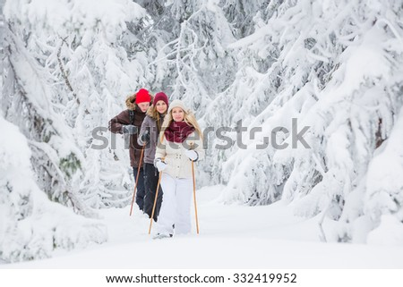 Young adults snowshoeing in snowy forest in winter - stock photo