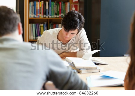Young adults working on an essay in a library
