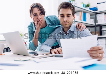 Young affectionate couple at home checking expensive bills, they are calculating balance and costs - stock photo