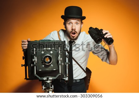 Young  afraid man in hat as photographer with retro camera and binoculars on an orange background - stock photo