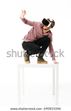 Young afraid man standing on white table in studio and take cover of something while playing with virtual reality glasses on white background. Amazed boy using visual reality glasses isolated