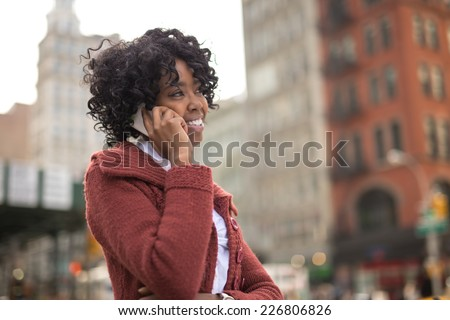 Young African American black woman in New York City talking on cellphone - stock photo