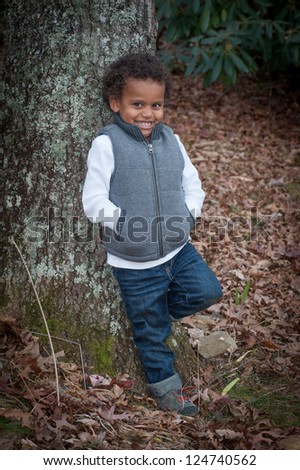 Young african-american boy standing by a tree for his portrait smiling for the camera.