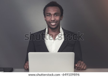 Young African American businessman sitting at his workplace and portraying success in business and good social skills. Toned image