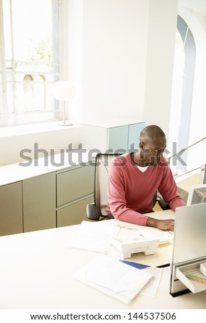 Young African American businessman working on computer at desk - stock photo
