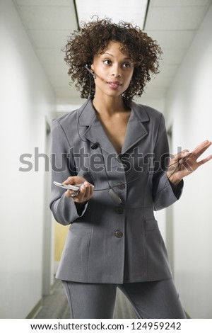 Young African American businesswoman talking on phone at workplace