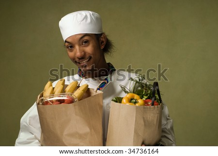 Young African American Chef Holding Brown Paper Bags full of Groceries - stock photo