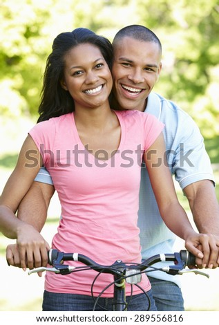 Young African American Couple Cycling In Park - stock photo