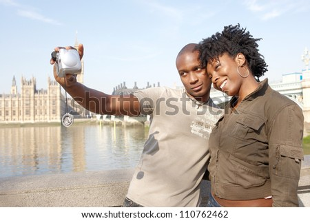 Young african american couple taking pictures of themselves while on vacations in London, standing in front of Big Ben.
