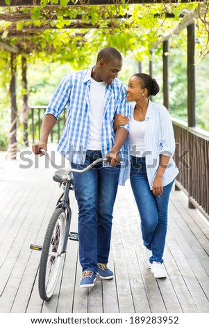 young african american couple walking with bicycle under grape vines - stock photo