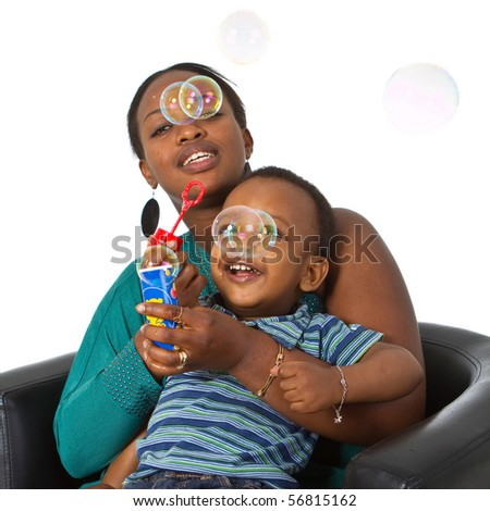 Young african american family playing around with bubbles. Fresh young image. - stock photo